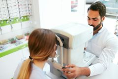 De Optometrist Testing Woman Eyesight van de oogtest op Modern Materiaal royalty-vrije stock afbeeldingen