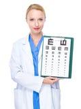De optometrist toont met ooggrafiek Stock Fotografie