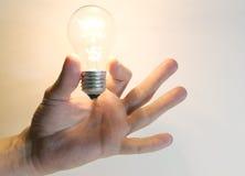 De opvlammende bol van de verlichtingslamp in menselijke hand Royalty-vrije Stock Fotografie