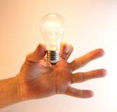 De opvlammende bol van de verlichtingslamp in menselijke hand Stock Afbeeldingen