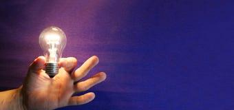 De opvlammende bol van de verlichtingslamp in menselijke hand op blauwe achtergrond Stock Fotografie