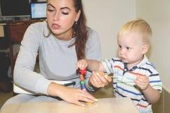 De opvoeder behandelt het kind in de kleuterschool Creativiteit en ontwikkeling van het kind stock fotografie
