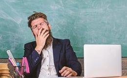 De opvoeders beklemtoonden meer op het werk dan gemiddelde mensen Moeheid op hoog niveau Opvoeder gebaard die mens geeuwgezicht o stock foto's