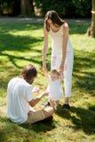 De opwindende moeder en de vader onderwijzen hun kleine dochter die witte kleding dragen hoe te om haar eerste stappen te maken stock afbeelding