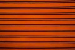 De oranje achtergrond van de het blinddeur van de staalrol (garagedeur met h Stock Afbeeldingen