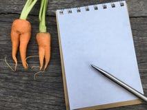 De oranje Babywortel kijkt als vrouwenvorm op houten achtergrond en ruimtenotitieboekje en pen Stock Foto's