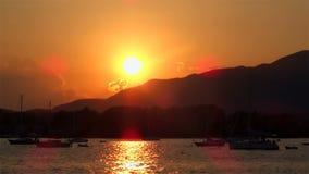 De oranje boten van de tijdspannewolken van de zonsondergangtijd en zwarte berg stock videobeelden