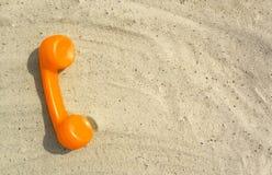 De oranje buis van een oude uitstekende telefoon ligt op het zand royalty-vrije stock afbeeldingen