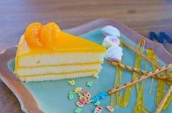 De oranje cake met Kleurrijk suikergoed bestrooit op plaat Stock Afbeeldingen