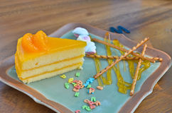 De oranje cake met Kleurrijk suikergoed bestrooit op plaat Stock Afbeelding