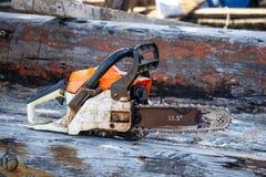 De oranje draagbare kettingzaag van de benzinemotor gezet op de oude houten plank royalty-vrije stock fotografie
