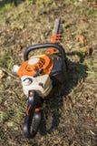 De oranje draagbare kettingzaag van de benzinemotor op een gras royalty-vrije stock afbeeldingen
