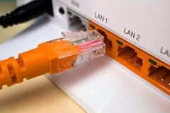 De oranje haven en de oranje kabel worden thuis verbonden met Internet stock foto's