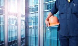 De oranje helm van de ingenieursholding voor arbeidersveiligheid Stock Afbeeldingen