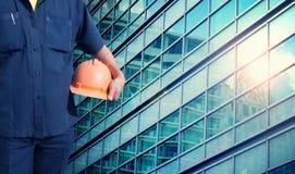 De oranje helm van de ingenieursholding voor arbeidersveiligheid Royalty-vrije Stock Foto