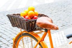 De oranje landelijke fiets van de Provence met vruchten in rieten mand stock afbeeldingen