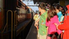 De oranje Passagierstrein komt aan Overvol Platform aan stock video