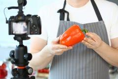 De Oranje Peper van chef-kokvlogger showing camcorder royalty-vrije stock foto's