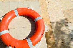 De oranje reddingsboei voor veiligheid van het zwemmen ligt op de steenvloer op een tropische mariene exotische zuidelijke warmte royalty-vrije stock afbeeldingen