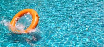 De oranje reddingsboei wordt geworpen aan duidelijk water zwembad Royalty-vrije Stock Fotografie