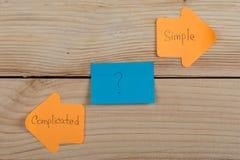 de oranje stickers van de het levenskeus in de vorm van indexpijlen met tekst Ingewikkeld en Eenvoudig op houten achtergrond royalty-vrije stock foto