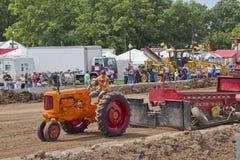 De oranje tractor die van Minneapolis Moline sporen trekt Stock Foto's