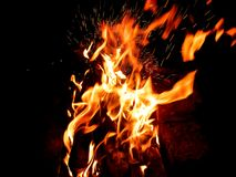 De oranje vlam met vonken, werd een kampvuur verlaten na het roosteren van de vleespennen brandwonden uit in dark stock afbeelding