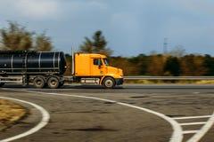 De oranje vrachtwagen met een tank berijdt op de weg, vage achtergrond Stock Afbeeldingen