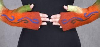 De oranje vuisthandschoenen van felted wol op de handen van het model Stock Foto's
