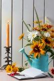 De oranje zomer bloeit als heliopsis, kamille, rudbeckia en gaillardia met notitieboekje, oude sleutel en pen Kandelaar stock foto's