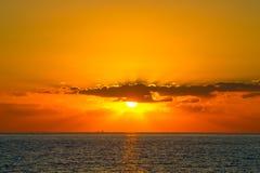 De oranje zonsondergang met stralen glanst door de wolken bij Paphos-coas Stock Afbeeldingen