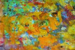 De oranjegele purpere gouden verf vertroebelde plonsen, kleurrijke levendige wasachtige kleuren, contrasten creatieve achtergrond royalty-vrije stock afbeeldingen