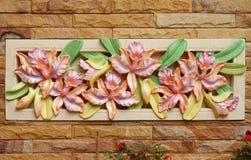 De orchideebeeldhouwwerk van de bloem op een muur Stock Afbeeldingen