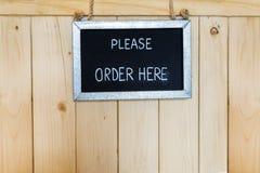 De orde ondertekent hier het hangen op houten achtergrond Royalty-vrije Stock Fotografie