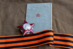 De orde van Red Star, soldier's boek en St George Ribbon ligt op een geteerd zeildoek Close-up 9 kunnen stock afbeelding