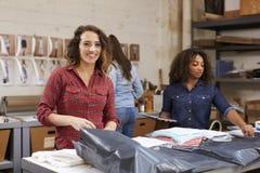 De orden van de teamverpakking voor distributie, vrouwenglimlachen aan camera royalty-vrije stock afbeelding