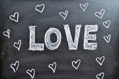 De ordförälskelsen och hjärtorna på en svart tavla Arkivfoto