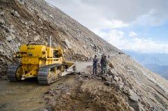 De organisatiepersoneel die van grenswegen een grondverschuiving met behulp van een aardeverhuizer ontruimen dichtbij Khardungla- royalty-vrije stock fotografie
