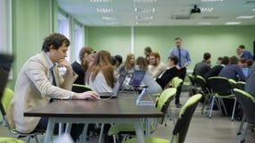 De organisator van zaken spelzitting bij het bureau in het klaslokaal en het gebruiken van laptop tijdens studenten bij de ruimte stock video
