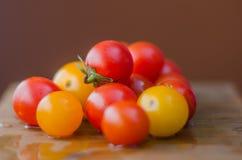 De organische kersentomaten van een tuin zijn gezonde gele rood stock foto's