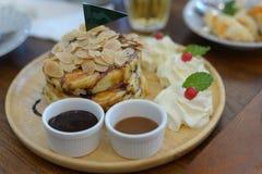 De Originele pannekoeken met amandelen en slagroom op houten schotel royalty-vrije stock foto's