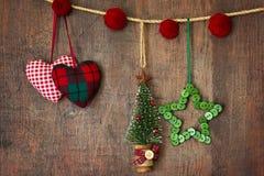 De ornamenten die van Kerstmis op hout hangen Stock Foto