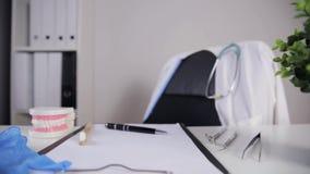 De orthodontische hulpmiddelen van de tanden model en professionele tandarts op de lijst in het bureau van de tandarts stock video