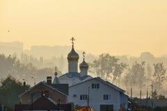 De Orthodoxe Kerk amid de ochtendmist Stock Foto