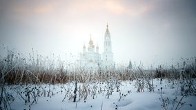 De Orthodoxe Kerk bij zonsondergang in de winter in mist Stock Foto's