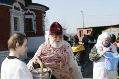 De orthodoxe priester bespat het wijwater Stock Foto's