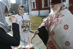 De orthodoxe priester bespat het wijwater Stock Fotografie