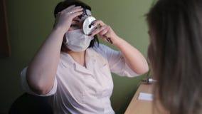 De otolaryngoloog onderzoekt een patiënt in kliniek stock footage