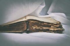 De oude antieke sjofele boek` Bijbel ` ligt open op de lijst met wit gordijn Het concept het onderwijs van Jesus stock afbeelding