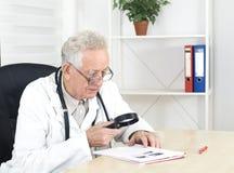 De oude arts met loupe bestudeert een literatuur Stock Fotografie